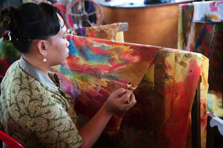 A local woman uses natural dyes to design a traditional batik in Bali