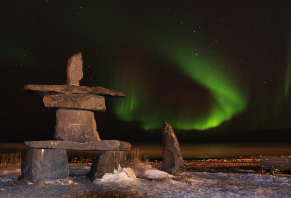Inukshuk under northern lights in Canada