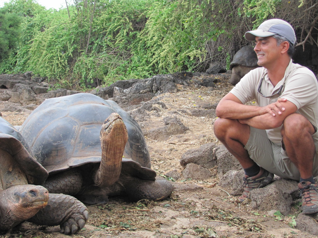 Expedition Leader, Roberto Plaza, enjoying a moment with the island's eponymous giant tortoise.© Holly Glessner/NHA