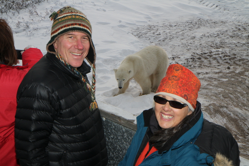 People pose with a polar bear on the tundra