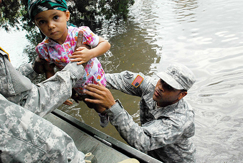 Climate change increases the probability of some types of weather. Flooding is consistent with a warming planet. Here, a soldier with the Louisiana National Guard evacuates a child from the flood waters caused by Hurricane Isaac in 2012. ©Sgt. Rashawn D. Price, U.S. Army