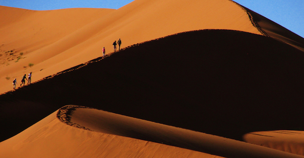 Travelers on a san dune in Namibia.