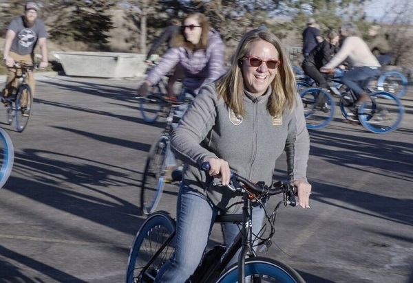 Shelby Campbell, Adventure Relations Director, joyfully rides her bike in the NHA parking lot.